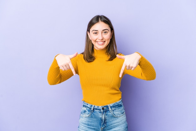 Young woman points down with fingers, positive feeling