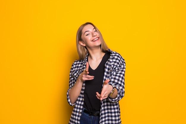 若い女性は、孤立した黄色の壁に笑みを浮かべながらあなたに指を指しています