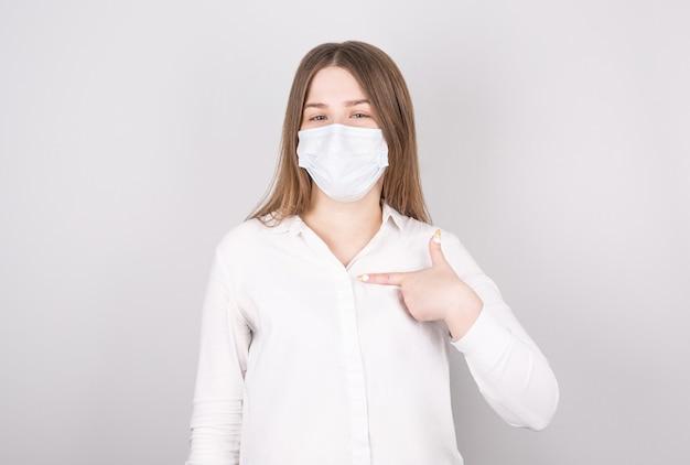 젊은 여자는 자신에게 그녀의 손가락을 가리 킵니다. 코로나 바이러스 감염 및 감기 예방을 위해 마스크 착용의 중요성을 보여줍니다.