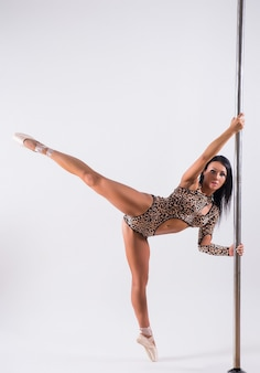 Young woman pole dancer isolated on white background