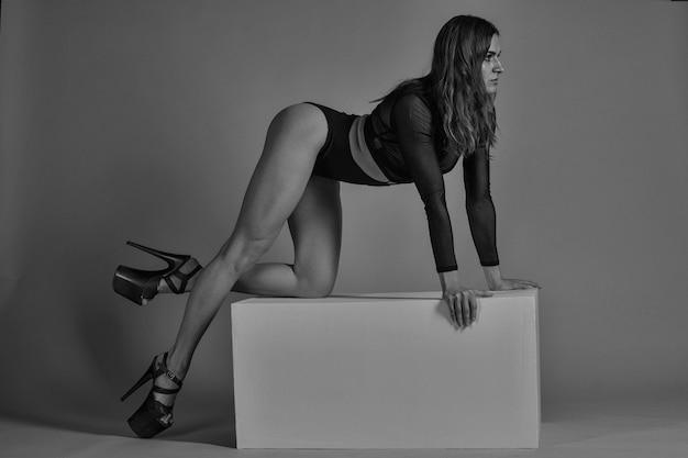Молодая женщина-танцор полюса позирует на кубе в стиле синхронной волны