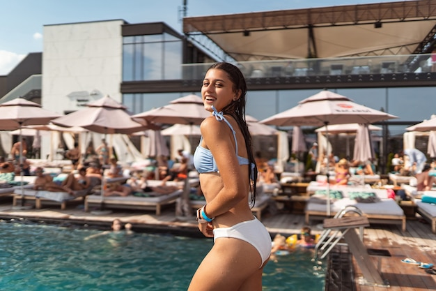Young woman in the pool in a white swimsuit