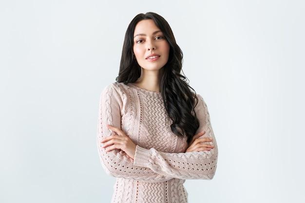若い女性の肖像画。彼女の腕を組んでポーズをとるセーターの愛らしいブルネット。