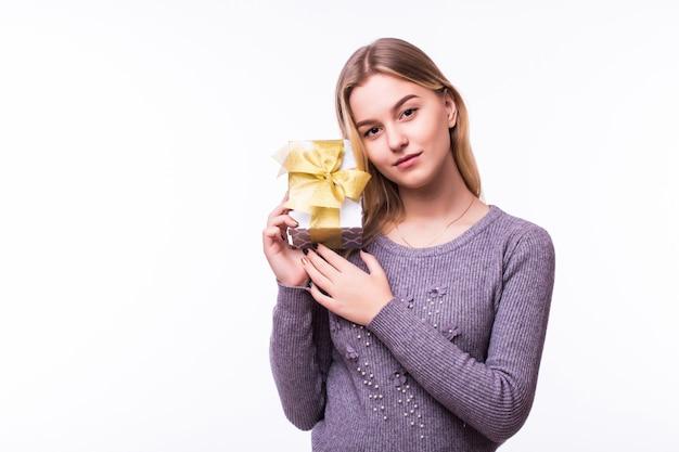 若い女性の肖像画は、クリスマスに贈り物を保持します。白い壁に幸せな女の子の笑顔。