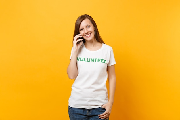 노란색 배경에 격리된 휴대 전화로 말하는 녹색 제목 자원 봉사자가 있는 흰색 티셔츠를 입은 젊은 여성 초상화. 자발적인 무료 지원 도움, 자선 은혜 작업 개념.