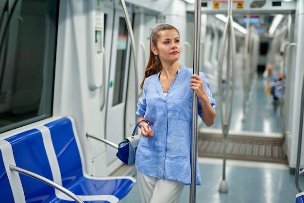 Портрет молодой женщины внутри метро. женщина стоит в вагоне метро.