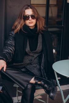 Ritratto di giovane donna seduta dal caffè