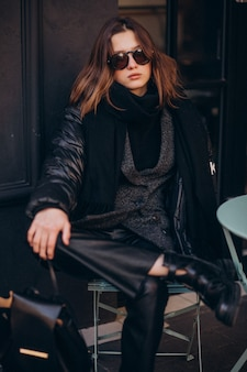 Портрет молодой женщины, сидя у кафе