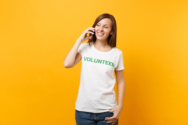 Young woman portrait in white t-shirt with written inscription green title volunteer talking on mobile phone isolated on yellow background. voluntary free assistance help, charity grace work concept.