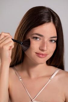 Ritratto di giovane donna con un prodotto per il trucco