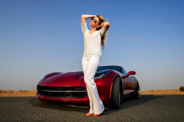 Молодая женщина позирует возле автомобиля в пустыне на закате.