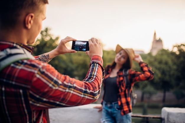 젊은 여자는 관광 마을 여행에 포즈. 사랑 한 쌍의 여름 하이킹. 젊은 남녀의 하이킹 모험