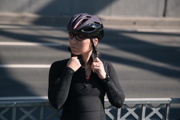 자전거 헬멧과 안경을 쓰고 훈련 후 포즈를 취하는 젊은 여성