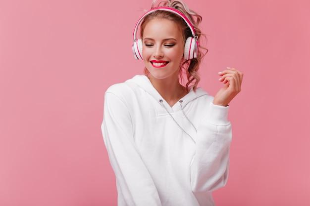 Молодая женщина позирует и слушает музыку через розовые наушники