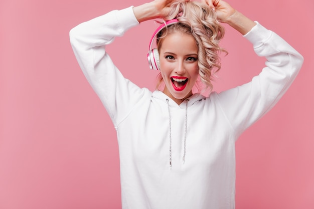 彼女のピンクのヘッドフォンでポーズをとって音楽を聴いている若い女性