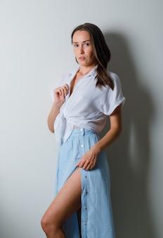 젊은 여자가 정면에서 포즈를 취하고 흰색 티셔츠와 밝은 파란색 치마에 치마에 손을 넣고 매력적인 찾고