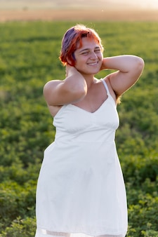 Young woman posing confidently outdoors in a field and showing armpit hair