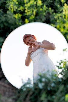 둥근 거울을 사용하여 야외에서 자신있게 포즈를 취하는 젊은 여성