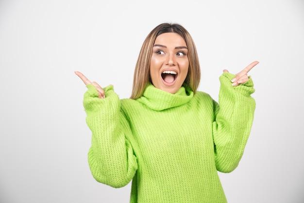 Giovane donna in posa in maglietta verde su un muro bianco