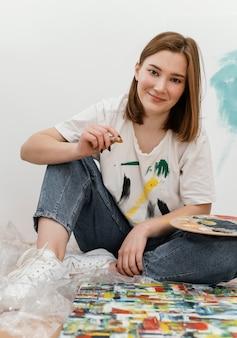 Giovane donna in posa accanto alla sua pittura colorata