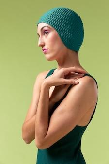 Молодая женщина позирует в зеленом купальнике