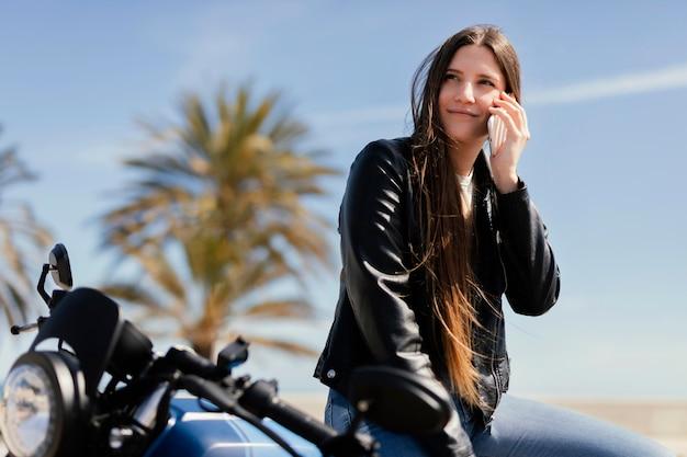 バイクでポーズをとる若い女性