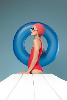 빨간 수영복을 입고 포즈를 취하는 젊은 여자