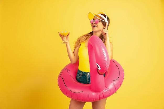 Молодая женщина позирует в пляжном кольце с коктейлем