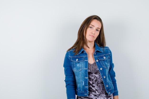 デニムジャケットでポーズをとって、賢明に見える若い女性、正面図。