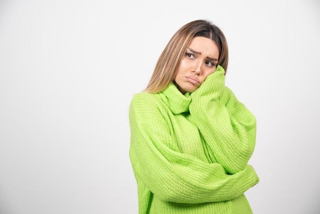 白い壁の上の緑のtシャツでポーズをとって若い女性