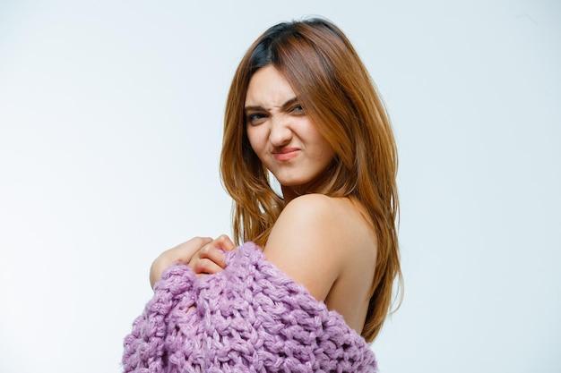 ニットウェアでポーズをとる若い女性