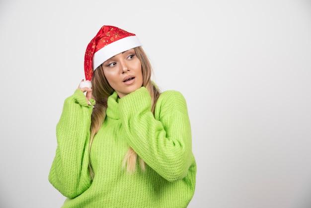 산타 클로스 빨간 모자에 포즈를 취하는 젊은 여자.