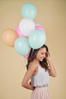 다채로운 헬륨 baloons의 무리와 함께 스튜디오에서 포즈를 취하는 젊은 여자