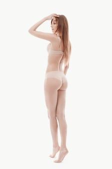 Молодая женщина позирует в нижнем белье, бежевый бюстгальтер и трусики, идеальная кожа, вид сзади