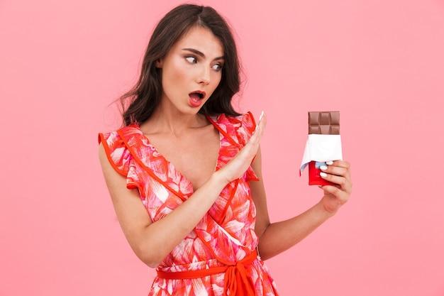 Молодая женщина позирует изолированной стене, держащей шоколад, показывая стоп-жест.