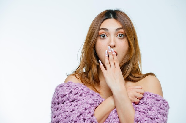 Young woman posing in knitwear and looking shocked