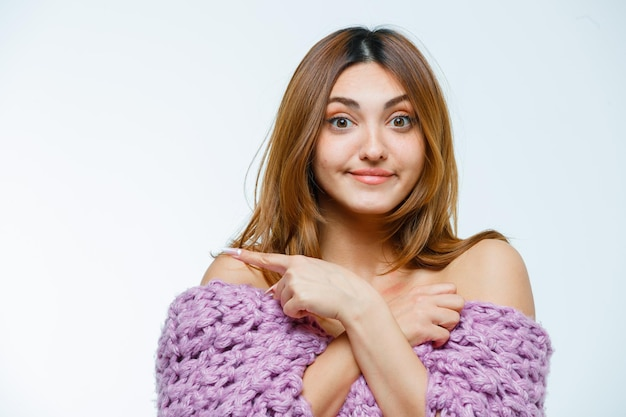 Young woman posing in knitwear and pointing