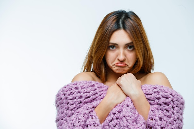 Young woman posing in knitwear and pouting lips