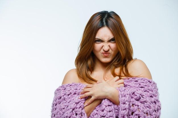 Giovane donna in posa in maglieria mentre mostra la faccia arrabbiata
