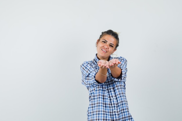 Young woman posing like sharing something in checkered shirt and looking pleased.
