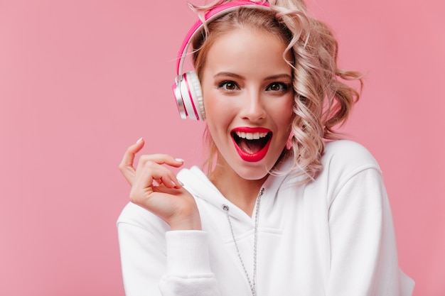Young woman posing and listening to music through her pink headphones