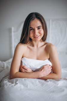 Young woman posing naked in bed