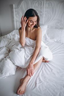 침대에서 알몸으로 포즈를 취하는 젊은 여자