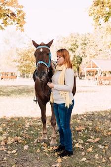 Молодая женщина позирует возле коричневой лошади в осеннем парке