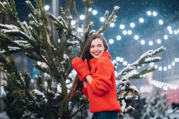Young woman posing near the christmas tree on the street