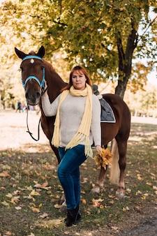 Молодая женщина позирует возле лошади с осенними листьями