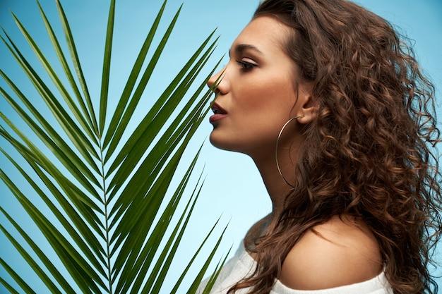 Young woman posing near palm leaf