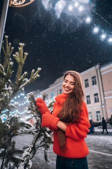 거리에서 크리스마스 트리 근처 포즈를 취하는 젊은 여자