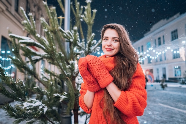 젊은 여자는 거리에 크리스마스 트리 근처 포즈