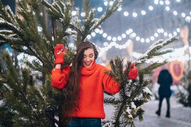 通りのクリスマスツリーの近くでポーズをとって若い女性